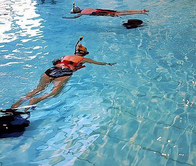 Auf diesem Bild bekommt man einen Ausschnitt vom VR-Schnorcheln im Nettebad in Osnabrück zu sehen. Im Wasser schwimmen zwei Frauen und sind dabei zu schnorcheln. Währenddessen tragen sie VR-Brillen.