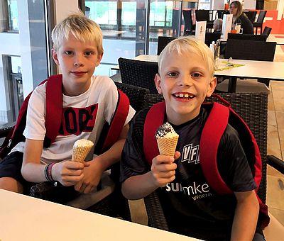 Auf diesem Foto sitzen zwei kleine blonde Jungen im Bistro vom Nettebad Osnabrück. Die Jungs gönnen sich nach dem VR-Schnorcheln ein Eis in der Waffel. Beide jungen tragen einen roten Rucksack auf dem Rücken. Der etwas größere Junge der am Fester sitzt, trägt ein weißes T-Shirt. Der andere junge trägt ein schwarzes VFL-Osnabrück T-Shirt.