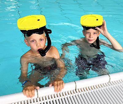 Auf diesem Bild geht es um das VR-Schnorcheln im Nettebad Osnabrück. Zwei kleine Jungen stehen mit der VR-Brille auf dem Kopf und dem Schnorchel im Wasser am Beckenrand. Der linke Junge hält sich mit beiden Händen am Wasserrand fest und hat seinen Schnorchel im Mund. Der rechte Junge hält seine VR-Brille mit der einer Hand an seinem Kopf fest.