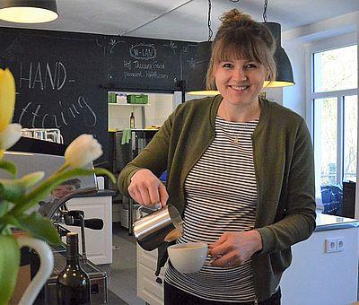 Im Ausflugslokal Hof Thiesing in Osnabrück gibt es vieles zu sehen und leckeren Kaffee. Auf diesem Foto steht eine Frau, die gerade dabei ist, Kaffee in eine weiße Tasse zu gießen. Neben der Frau steht eine Blumenvase mit bunten Tulpen. Die Wand hinter der Frau ist schwarz gestrichen und es ist mit einer weißen Schrift etwas drauf geschrieben, was man leider nicht lesen kann. Links hinter den Tulpen steht eine große silberne Kaffeemaschine.