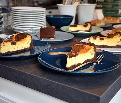 Im Ausflugslokal Hof Thiesing in Osnabrück könnt ihr auch leckeren Kuchen essen. Auf diesem Foto liegen die einzelnen Kuchenstücke zum Servieren bereit. Jeweils zwei Kuchenteller stehen nebeneinander und dahinter. Insgesamt sieht man auf diesem Foto zwölf Kuchenteller mit jeweils einem Stück Kuchen. Die ersten beiden Kuchenteller sind dunkelblau und mit jeweils einem Käsekuchenstück und einer Kuchengabel bestückt. Dahinter liegen auf weißen Tellern weitere drei Käsekuchenstücke. Hinter den Käsekuchenstücken liegen weitere Kuchenstücke. Dies sind vermutlich Stückchen mit Apfelkuchen. Links neben den Kuchenstücken steht aufgestapelt weißes Geschirr.
