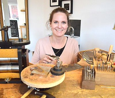 Im Ausflugslokal Hof Thiesing in Osnabrück gibt es auch eine Goldschmiede (Goldmari) und dieses Foto gibt einen Einblick, wie es in der Goldschmiede aussieht. An einem abgerundeten Holztisch sitzt eine junge braunhaarige Frau, die in die Kamera lächelt. Sie ist eine Goldschmiedin und ist gerade dabei, einen goldenen Ring zu bearbeiten. Rechts neben der Frau, auf dem Holztisch, stehen verschiedene Werkzeuge in einer Holzbox. Vor der Frau steht außerdem ein runde Korkscheibe, die sich drehen lässt.