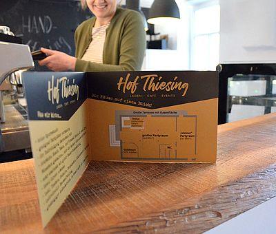 Einen Einblick von der Theke im Ausflugslokal Hof Thiesing in Osnabrück bekommt ihr auf diesem Bild. Hier steht eine geöffnete Speisekarte auf der Holztheke. Wenn man genauer hinsieht, ist es gar keine Speisekarte. In der kleinen Broschüre ist ein Plan von Hof Thiesing abgedruckt. Hier sieht man den kleinen Partyraum, den großen Partyraum und die Goldschmiede Goldmari. Hinter der Theke steht eine Frau an der Kaffeemaschine. Die Frau ist aber nicht ganz zu sehen, da das Bild über ihrer Nase aufhört, ihre Augen und Haare sind nicht mehr auf dem Bild zu sehen.