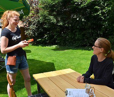 Das Foto wurde aufgenommen auf Hof Thiesing, einem Ausflugslokal in Osnabrück. Eine junge rothaarige Frau, die ein schwarzes T-Shirt mit einem weißen Logo von Hof Thiesing trägt, bedient eine andere Frau, die im Biergarten an einen Holztisch sitzt. Auf dem Tisch liegt eine Speisekarte & eine Tischnummer mit der Nummer vier.