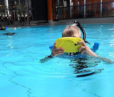 Auf diesem Foto bekommt man einen Einblick, wie das VR-Schnorcheln im Nettebad Osnabrück aussehen kann. Im Schwimmbecken ist ein kleiner blonder Junge zu sehen, der gerade dabei ist zu schnorcheln. Mit seiner gelben VR-Brille, die er mit beiden Händen auf seinen Kopf trägt, kann er sich in eine andere Welt versetzen.