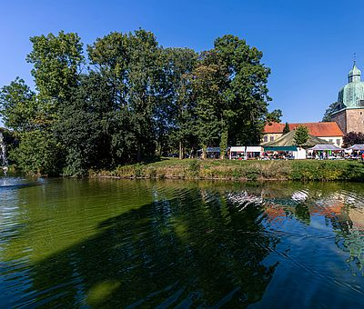 Dieses Foto ist beim Sommerfest der Kulturen in Fürstenau im Osnabrücker Land entstanden. Im Bildvordergrund ist Wasser mit einer kleinen Wasserfontäne zu sehen, am Ufer dahinter ist die Schlossinsel von Fürstenau zu erkennen. Hier stehen ein paar grüne Bäume und rechts neben den Bäumen ist eine grüne Wiese. Hinter der Wiese sieht man offene Zelte und Verkaufsstände stehen. Hinter den offenen Ständen sieht man ein weißes Haus mit roten Dachpfannen, das Haus kann man aber nur zum Teil sehen, da davor die Zelte stehen. Links neben dem weißen Haus ist eine Kirche mit einer bronzenen, grün oxidierten Turmhaube zu erkennen. Der Himmel ist strahlend blau und wolkenlos.