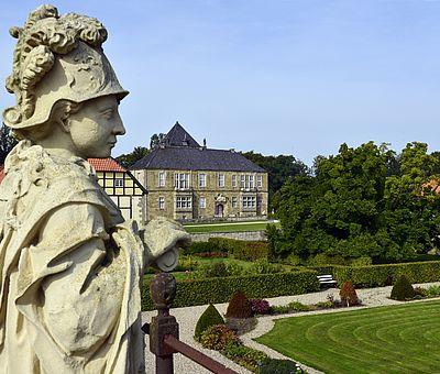 Sandsteinfiguren blicken auf die gelungene Wiederherstellung des Barockgartens von Schloss Gesmold bei Melle. In der ehemaligen Orangerie befindet sich heute ein Bio-Café.