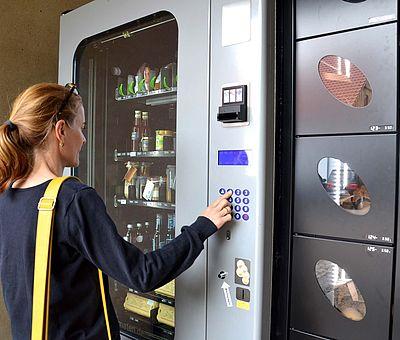 Auf diesem Foto vom Ausflugslokal Hof Thiesing in Osnabrück bekommt ihr einen Einblick, wie der Selbstbedienungsautomat funktioniert. Eine junge Frau steht vor dem Selbstbedienungsautomaten und tippt mit dem rechten Zeigefinger eine Zahl ein, um ein Produkt zu kaufen. In dem Automaten könnt ihr frische Eier, Honig und noch viele weitere Lebensmittel frisch vom Hof kaufen. Am Automaten können Gäste, auch wenn der Hof geschlossen hat, frische Lebensmittel gegen Kleingeld bekommen. Er steht 24 Stunden an 7 Tagen für alle offen.