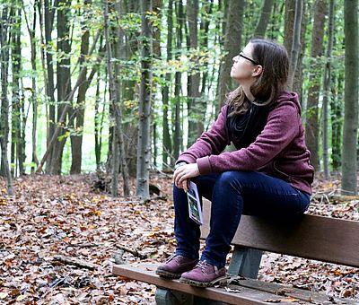 Auf diesem Foto sitzt eine braunhaarige junge Frau auf einer Parkbank und genießt mitten im Wald neben vielen Bäumen und bunten Herbstblättern den Gesundheitspfaden in Bad Essen. Dies ist ein Wanderweg, der zum Genuss mit allen Sinnen einlädt. Eine kleine Pause, um zwischendurch kräftig Durchzuatmen gehört auf einer Wanderung natürlich auch dazu. Nach der kurzen Pause geht es fit weiter mit dem Spaziergang.