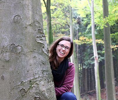 Auf einer Wanderung steht der Spaß im Vordergrund. Auf diesem Bild sitzt eine junge braunhaarige Frau hinter einem Baum und lacht in die Kamera. Im Hintergrund sieht man die herbstliche Natur mit bunten Blättern auf dem Boden und in den Bäumen. So macht die Wandertour über die Gesundheitspfade in Bad Essen allen Sinnen Spaß und hält fit.